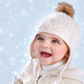 Wintertime baby fashion closeup portrait of cute little girl wearing warm stylish hat isolated on blue snowy background snow Royalty Free Stock Image