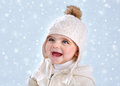 Wintertime baby fashion portrait of cute little girl wearing warm stylish hat on blue snowy background snow falling winter season Stock Photo
