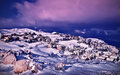 Wintertime village landscape beautiful of mountainous in dramatic purple sunset houses covered with snow celebrating christmas Royalty Free Stock Photos