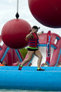 Wipeout k run obstacles course wrecking balls woman running at the water obstacle at the in wilmington delaware the is Royalty Free Stock Images