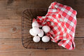 Wire basket and eggs a with a red checkered napkin on a rustic wood surface overhead shot looking straight down into the Stock Image