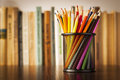 Wire desk tidy full of coloured pencils standing on a wooden table in front a bookshelf books with shallow dof and Stock Photography