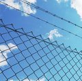 Wire fence with white clouds and blue sky background Royalty Free Stock Photo