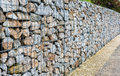 Wire Gabion Rock Fence. Metal Cage filled with rocks. Royalty Free Stock Photo