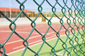 Wire metal mesh against a tennis court - concept image