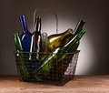 A wire shopping basket filled with empty bottles assorted the is sitting on rustic wooden table light to dark gray Stock Photography