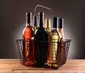 A wire shopping basket filled with wine bottles assorted the is sitting on rustic wooden table light to dark gray Royalty Free Stock Photography