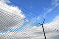 Wired fence and blue sky in background Royalty Free Stock Images
