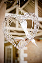 Wired heart decorative suspended from the ceiling with a white ribbon at the wedding Stock Photos