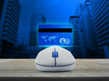 Wireless computer mouse with blue credit card on wooden table over city tower background, Online e-payment concept