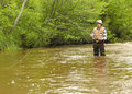 Wisconsin trout fishing fisherman in waders on an inland freshwater stream Stock Images