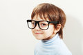 Wise little boy looking through big clear glasses Royalty Free Stock Photography