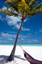 Wish you were here a beautiful tropical beach invites the viewer to relax and dream of being the person in the hammock Stock Photo