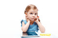 Wishful thinking young girl is using tablet while sitting at table, Royalty Free Stock Photo