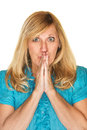 Wishful woman in suspense blond with hands together Stock Photo