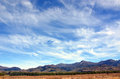 Wispy clouds in blue skies above mountain range Royalty Free Stock Photo