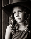 Wistful little girl in cowboy hat sitting barn with light on her face wearing and looking Stock Photos