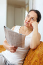 Wistful mature woman with newspaper serious and Stock Image