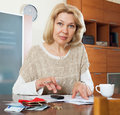 Wistful mature woman thinking about the financial issue at home Stock Images