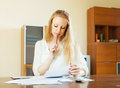 Wistful woman calculating something at home Stock Photos