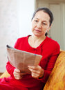 Wistful woman reading newspaper at home Stock Image