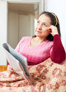 Wistful woman reading newspaper mature reads at home Stock Photo