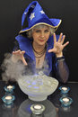 Witch in blue hat with magic crystals and candles Royalty Free Stock Photo