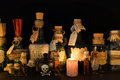 Witch bottles with candle on black Royalty Free Stock Photo