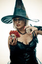 Witch casts a spell pretty blonde in the costume holding doll head and Royalty Free Stock Photos