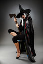Witch full length shot of a sorcerer with hat and cape over gray background holding an axe Royalty Free Stock Photos