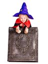 Witch girl holding book little thumb up Royalty Free Stock Photography