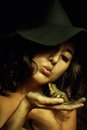 Witch and her breakfast naked in hat with frog in hand over dark background Royalty Free Stock Image