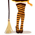 Witch legs broom closeup of woman in sexy halloween costume with mini skirt orange and black stripes stockings heel shoes and Royalty Free Stock Photo
