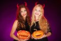 Witches with horns portrait of two horned females carved halloween pumpkins looking at camera Royalty Free Stock Photo