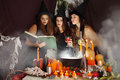 Witches look into the book of magical recipes Stock Photography