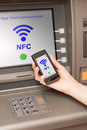 Withdrawing money atm with mobile phone a nfc terminal from Stock Photos