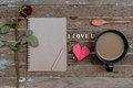 Withered rose and cup of coffee red heart shape notebook on old wooden background Stock Image