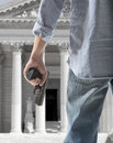 Witness protection security man holding gun against an courthouse background Royalty Free Stock Photography
