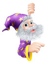 Wizard peeking round sign a cartoon a and pointing at it Royalty Free Stock Photography