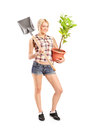 Wman holding shovel and a plant full length portrait of woman isolated on white background Stock Photo