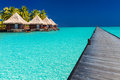 Wodden jetty extended into azure water of lagoon with villas ove long over the Stock Images
