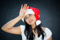 Woe is me closeup portrait of annoyed woman in santa claus hat hand on forehead playing tragedy expressing holiday stress on grey Stock Photos