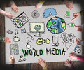 Wold media concept of information with illustrations and people around the table Royalty Free Stock Photo