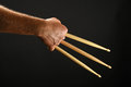 Wolverine hand with three drumsticks over black famous claws heroic gesture man holding wooden background back view horizontal Royalty Free Stock Photos