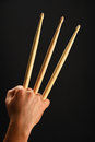 Wolverine hand with three drumsticks over black famous claws heroic gesture man holding wooden background back view vertical Stock Photo