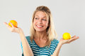 Woman with acidic fruits held in both hands for beauty diet natural vitamins concept smiling young blond balancing fresh studio Stock Image