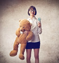 Woman acting like a kid holding lollipop and huge teddy bear Royalty Free Stock Images