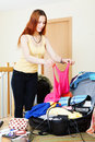 Woman adding clothes into suitcases long haired for vacation Stock Image