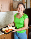 Woman adds cheese to stuffed vegetable marrow Royalty Free Stock Photography