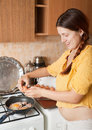 Woman adds eggs to hot skillet Royalty Free Stock Photos